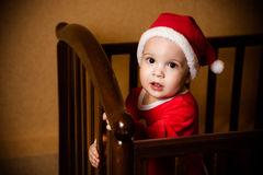 Kid dressed as Santa Claus stands in crib Royalty Free Stock Photography