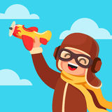 Kid dressed like a pilot playing with toy plane Stock Images