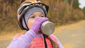 Kid drink water from an aluminum flask. One caucasian children rides bike road in autumn park. Little girl riding black. Kid drink water from an aluminum flask stock footage