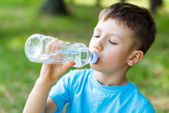 Kid drink water. Little boy drink water, outdoor royalty free stock photo