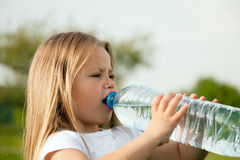 Kid drinking bottled water Royalty Free Stock Image