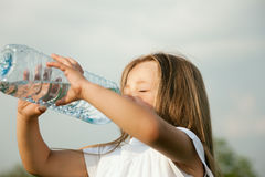 Kid drinking bottled water Royalty Free Stock Images