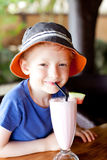 Kid drinking cocktail. Little kid drinking milk shake at the resort enjoying summer vacation Stock Image