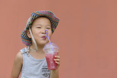 Kid drinking cold drink. Chinese happy kid drinking cold drink in summer with red background Stock Photo