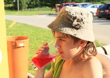 Kid drinking a drink. Little kid - boy in hat drinking a glass of non-alcoholic red drink Stock Images