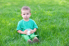 Kid drinking milk. A cheerful kid is sitting on the green grass having his mouth full with milk stock images