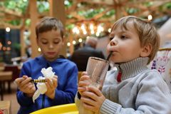 Kid drinking milk shake. At table in restaurant Stock Photography