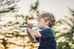 Kid drinking pure fresh water in nature at sunset.  Royalty Free Stock Photo