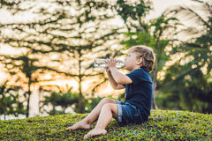 Kid drinking pure fresh water in nature at sunset royalty free stock photos