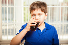 Kid drinking soda from a glass. Portrait of a young boy drinking soda from a glass at home royalty free stock photo