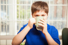 Kid drinking some coffee. Young boy drinking some coffee from a mug and making eye contact royalty free stock photography
