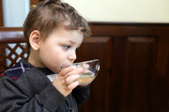 Kid drinking tea Stock Images