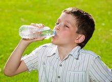 Kid drinking water stock image