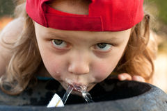 Kid drinking from water fountain. Thirsty little girl drinking from water fountain Stock Images