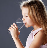 Kid drinking water from glass Stock Photo