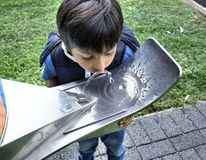 Child drinking water from public tap stock image
