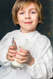 Kid drinks a glass of milk. Milkman boy holding a glass of milk Royalty Free Stock Photos
