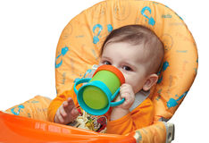 Kid drinks juice from the drinking bowl. Child drinks juice from the drinking bowl for the child table. Joyful kid sitting at a orange baby table Stock Images