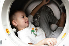 Kid in the dryer. Portrait of a kid in the dryer stock photography