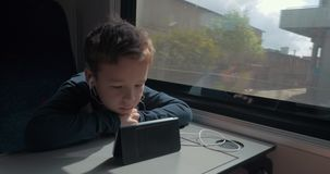 Kid with earphones watching cartoon on cell in train. Boy using earphones and smart phone to watch movie or cartoon during the train ride stock video