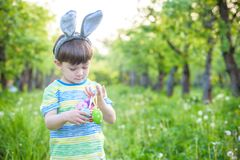 Kid on Easter egg hunt in blooming spring garden. boy searching. For colorful eggs in flower meadow Stock Images