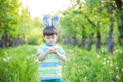 Kid on Easter egg hunt in blooming spring garden. boy searching. For colorful eggs in flower meadow Stock Photo