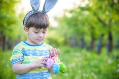 Kid on Easter egg hunt in blooming spring garden. boy searching for colorful eggs in flower meadow.  Royalty Free Stock Photo