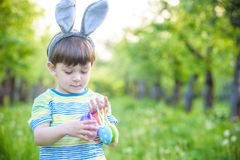 Kid on Easter egg hunt in blooming spring garden. boy searching for colorful eggs in flower meadow.  Stock Images