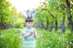 Kid on Easter egg hunt in blooming spring garden. boy searching. For colorful eggs in flower meadow Royalty Free Stock Photography