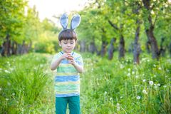 Kid on Easter egg hunt in blooming spring garden. boy searching. For colorful eggs in flower meadow Royalty Free Stock Images