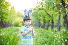 Kid on Easter egg hunt in blooming spring garden. boy searching. For colorful eggs in flower meadow Royalty Free Stock Image