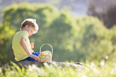 Kid at easter. Happy smiling boy excited after easter egg hunt in the park with basket full of eggs, spring concept Stock Image
