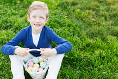 Kid at easter time. Beautiful smiling boy holding basket with colorful eggs after easter egg hunt Stock Image