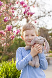 Kid at easter time. Cute little boy with plush bunny toy at easter and spring time with blooming magnolia in the background stock photography