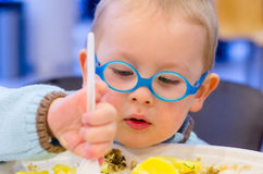 Kid eat dinner Stock Images