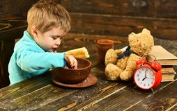 Kid eat food at wooden table. Kid enjoy meal with toy friend. Kid menu. Little kid eating. You are what you eat.  stock photos