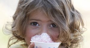 Kid eating. A picture of a cute little girl smiling eating snow cone stock images