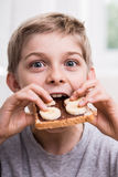 Kid eating with appetite. Smiling kid eating sweet sandwich with appetite Stock Photography