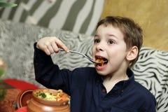 Kid eating baked vegetables Stock Photo