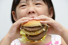 Kid eating big burger. Little girl with big burger or sandwich inside mouth Royalty Free Stock Photos
