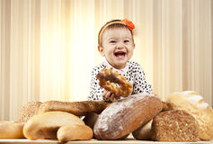 Kid eating bread. White infant choosing bread in studio Royalty Free Stock Images