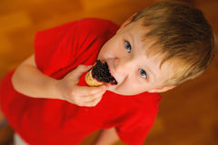 Kid eating bread with bilberry jam Stock Photos