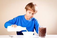 Kid eating breakfast. Boy pouring milk into a bowl of cereal. Child eating breakfast. Boy pouring milk into a bowl of cereal stock photo