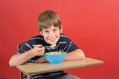Kid eating cereal at desk Royalty Free Stock Images