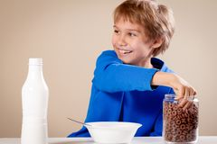 Kid eating cereal with milk for breakfast. Child eating cereal with milk for breakfast at home stock image