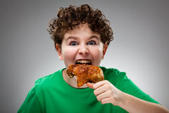 Kid eating chicken leg Stock Photos