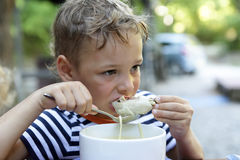 Kid eating chicken soup. In a restaurant Royalty Free Stock Images