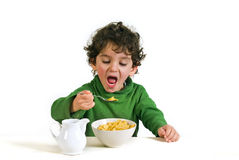 Kid eating cornflakes. Young boy eating cornflakes isolated on white Royalty Free Stock Photos