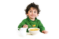 Kid eating cornflakes. Young boy eating cornflakes isolated on white Stock Images