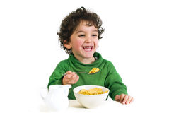 Kid eating cornflakes. Young boy eating cornflakes isolated on white Royalty Free Stock Photo